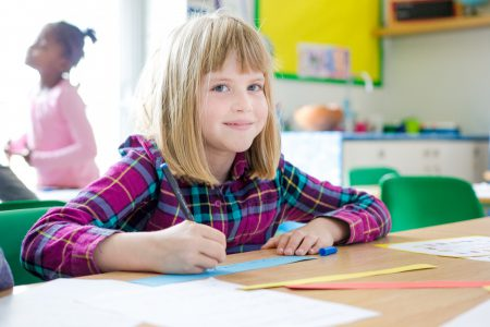 rhodes-avenue-photo-ks1-classroom-girl-smiling-and-writing